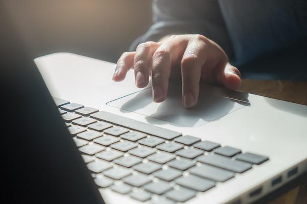 Dedo da mulher tocando no laptop touch pad