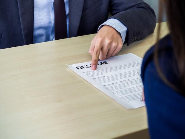 Dedo de empresário apontando em seu perfil no currículo ou papel do currículo na mesa