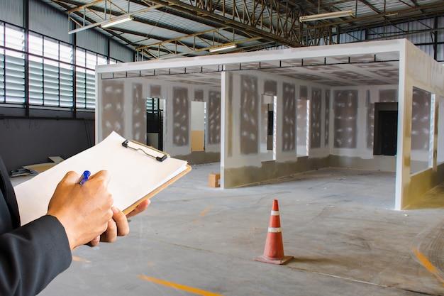 Dedo de engenheiro masculino apontando na fábrica com nota no bloco de notas