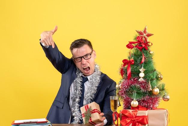 Dedo de homem bravo de vista frontal apontando para baixo sentado à mesa perto da árvore de natal e presentes em fundo amarelo