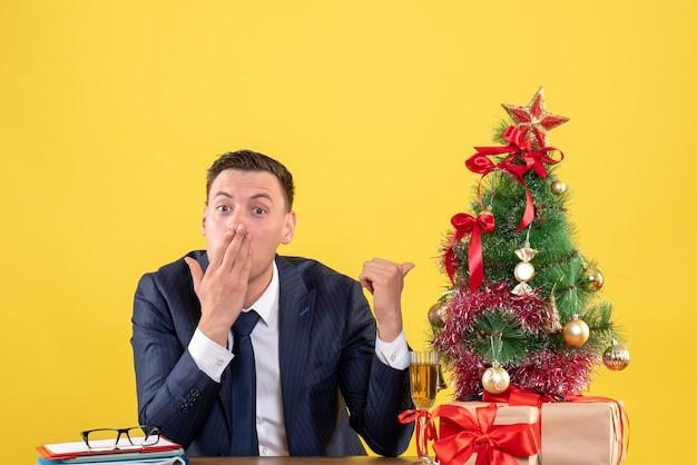 Dedo de homem espantado de vista frontal apontando a árvore de natal sentado à mesa perto da árvore de natal e presentes em fundo amarelo