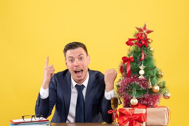 Dedo de homem espantado de vista frontal apontando para cima sentado à mesa perto da árvore de natal e presentes em fundo amarelo