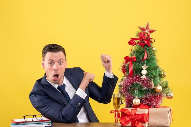 Dedo de homem espantado de vista frontal apontando para trás sentado à mesa perto da árvore de natal e presentes em fundo amarelo