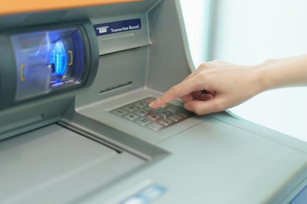 Dedo de mulher, pressionando um botão do caixa automático (atm)