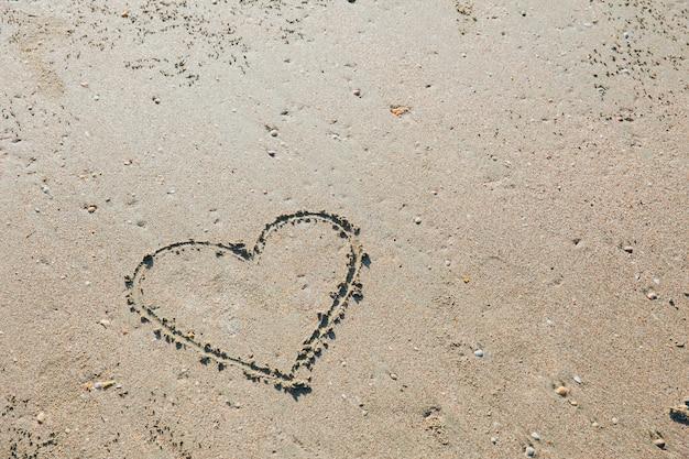 Dedo desenhado coração símbolo de amor no conceito de verão mar praia areia férias