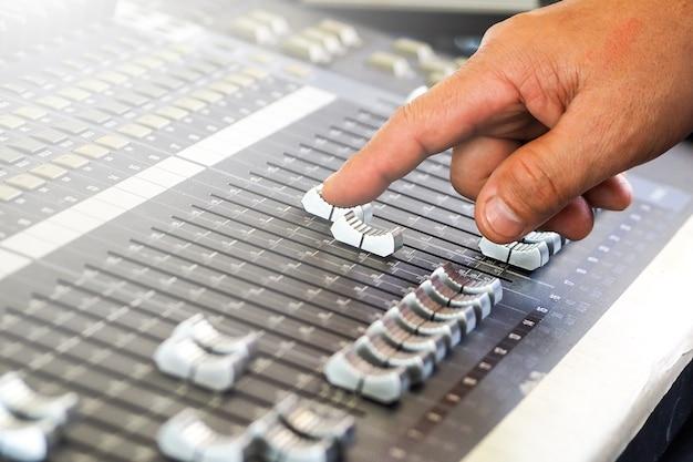 Dedo do homem ou dj ajustando o equalizador de áudio em concerto ou estúdio
