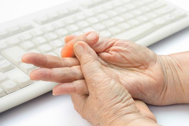 Dedo dolorido de mulher idosa devido ao uso prolongado de teclado e mouse.