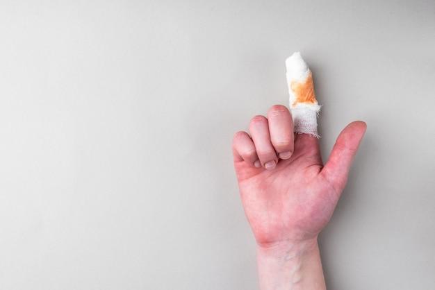 Dedo dolorido ferido com atadura de gaze branca