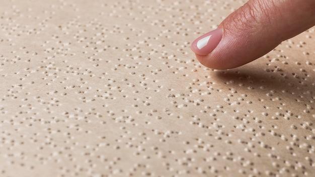 Dedo em close tocando a página braille