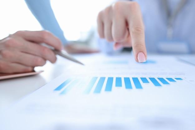 Dedo feminino apontando para o gráfico em close do documento