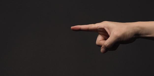Dedo indicador apontando para algo, isolado no fundo preto.