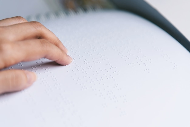Dedo ler o texto braille em papel branco.