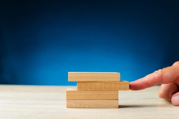 Dedo masculino empurrando um pino de madeira em branco em segundo lugar do topo em uma pilha deles em uma imagem conceitual. sobre fundo azul com espaço de cópia.