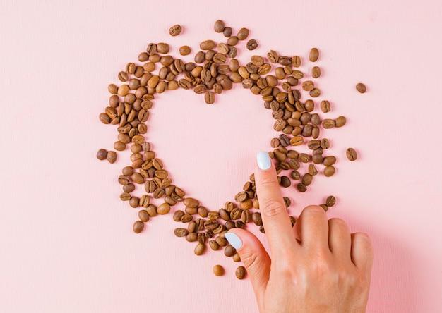 Dedo mostrando coração gap de grãos de café