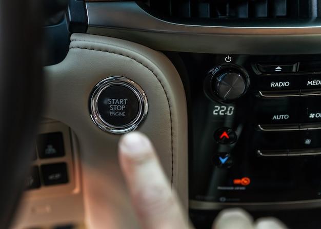 Dedo pressionando o botão de partida, desligue o motor no carro de luxo que o dedo do homem está