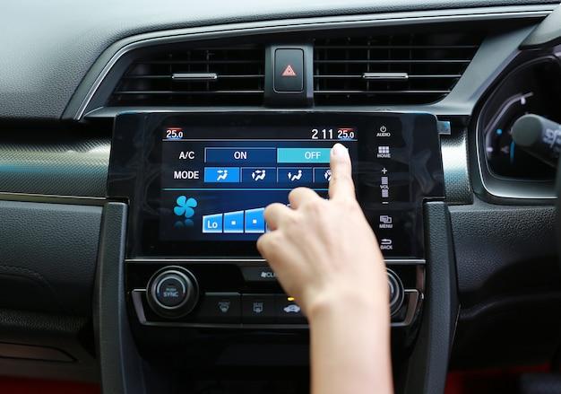 Dedo pressionando o botão do ar condicionado no painel do carro moderno
