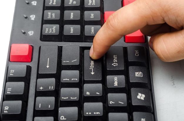 Dedo pressionando o botão enter no teclado