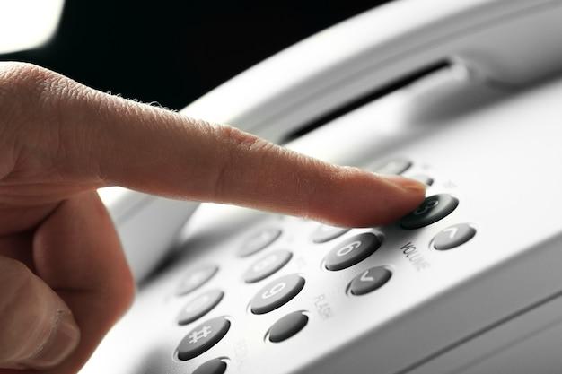 Dedo pressionando o botão numérico no telefone para fazer uma chamada, close-up