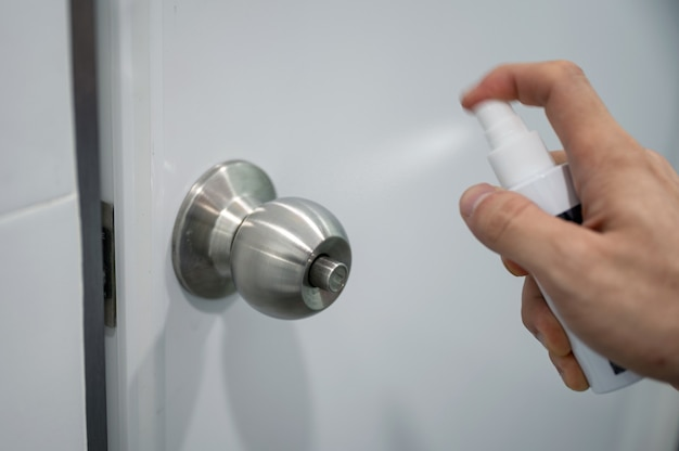 Dedo pressionando spray de álcool na maçaneta da porta do banheiro. infecção comprovada de coronavírus, desinfetantes covid-19