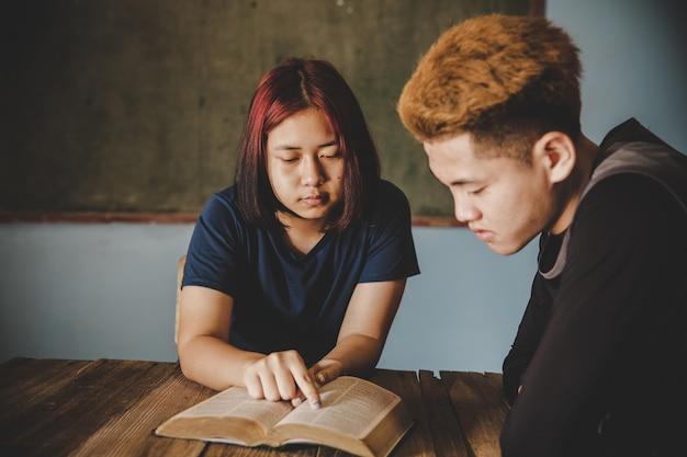 Dedos adolescentes apontando letras dentro da bíblia com uma sensação de alegria.