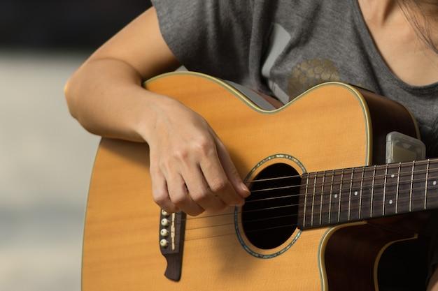 Dedos da menina tocar violão no parque