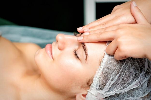 Dedos da terapeuta fazendo massagem anti-envelhecimento das rugas da testa em uma jovem mulher caucasiana em um salão de beleza do spa