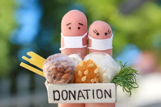 Dedos de arte de casal com máscara facial segurando uma caixa de doação com comida