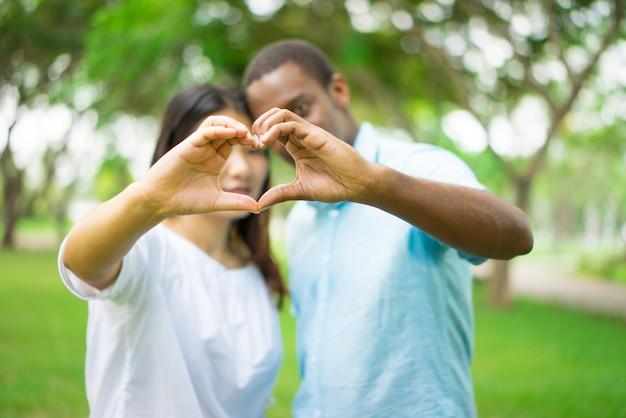 Dedos de junção dos pares inter-raciais na forma do coração ao ter data no parque do verão.