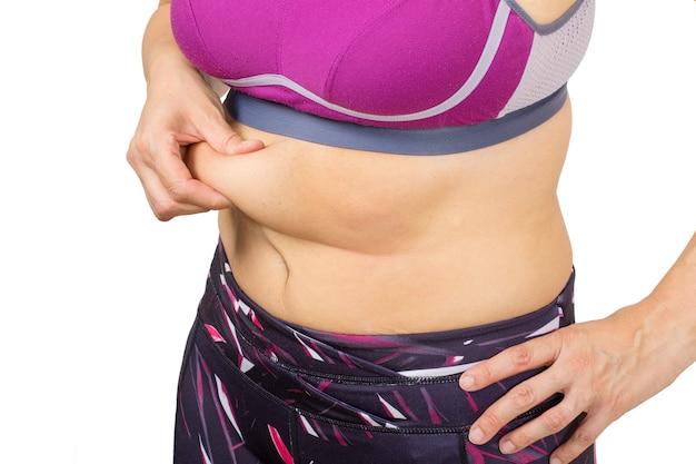 Dedos de mulher medindo a gordura da barriga