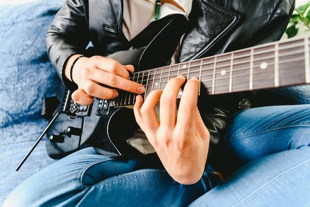 Dedos de um guitarrista colocados no traste do mastro da guitarra tocando um acorde fazendo tapping.