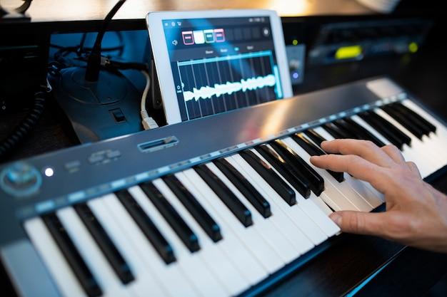 Dedos de um jovem pianista contemporâneo pressionando as teclas do teclado do piano enquanto grava música no local de trabalho em estúdio