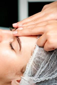 Dedos de vista lateral de uma terapeuta fazendo massagem antiidade de rugas na testa em uma jovem mulher caucasiana em um salão de beleza do spa