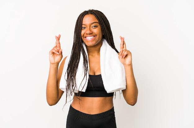 Dedos do cruzamento da jovem mulher afro-americana do esporte por ter sorte