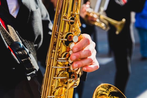 Dedos do saxofonista que jogam uma parte durante um festival da rua.