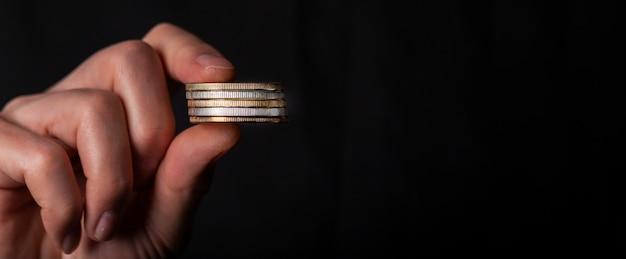 Dedos masculinos segurando uma pilha de moedas. conceito de lavanderia de dinheiro, contabilidade falsa preta. banner com espaço de cópia de texto.