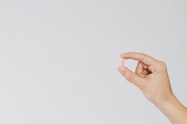 Dedos que prendem o comprimido