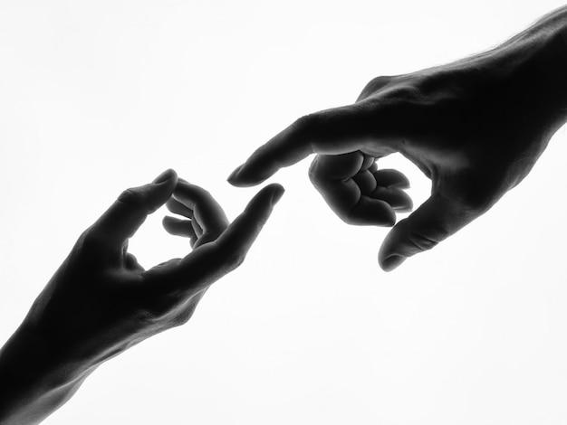 Dedos que tocam nas mãos do homem e da mulher - silhueta preto e branco isolada.