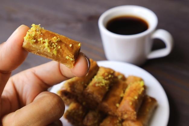 Dedos segurando uma pastelaria de baklava com pistache e café turco embaçado
