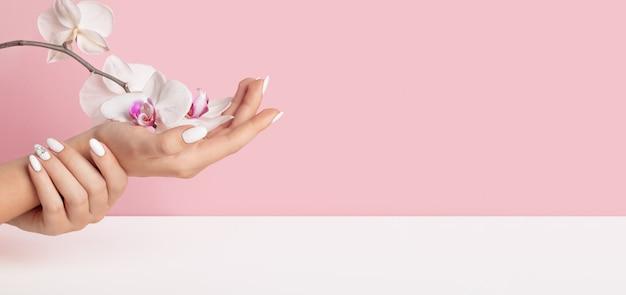 Dedos sutis das mãos de uma bela jovem com unhas brancas em um fundo rosa com flores da orquídea.