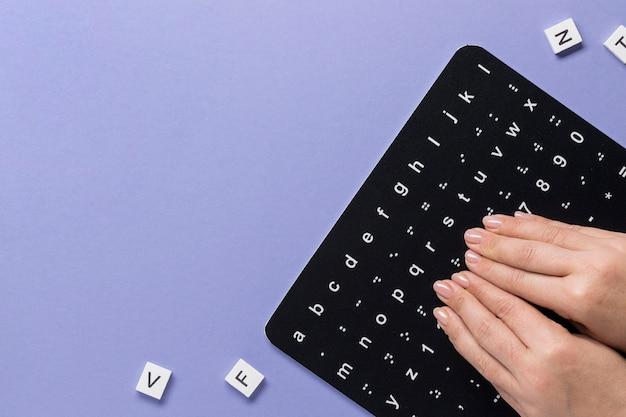 Dedos tocando a vista superior do quadro do alfabeto em braille