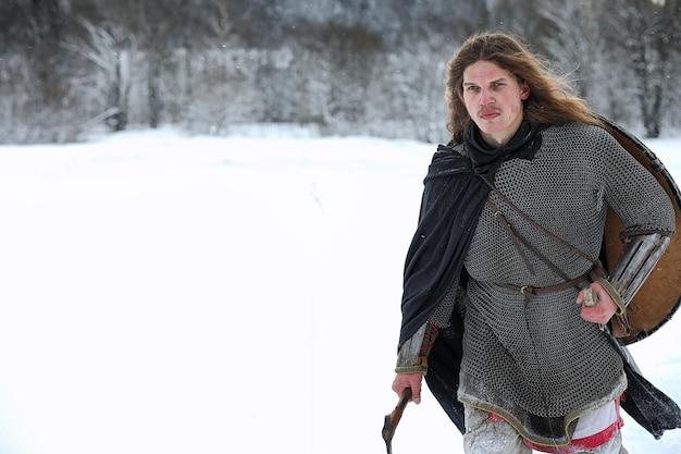 Defenda o jovem guerreiro em armadura de malha armado com uma espada e um machado