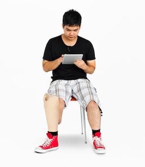 Deficiência jovem com prótese perna usando tablet studio por