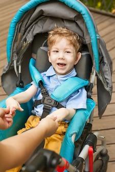 Deficiência: uma criança com deficiência em cadeira de rodas repousa na rua. o conceito de uma vida feliz.