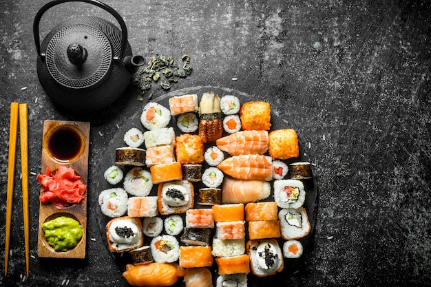 Defina uma variedade de rolos, sushi e maki com chá verde. em superfície rústica escura