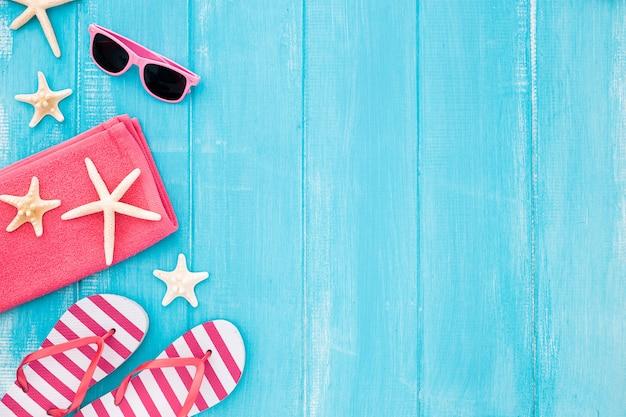 Definido para umas férias no mar praia: toalha, óculos de sol e estrelas do mar