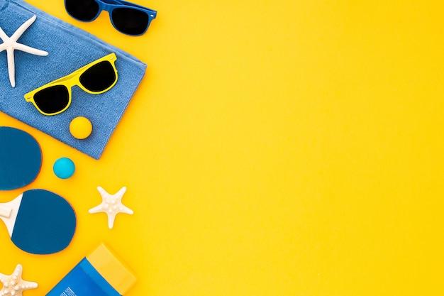 Definido para umas férias no mar praia: toalha, óculos de sol e suncream