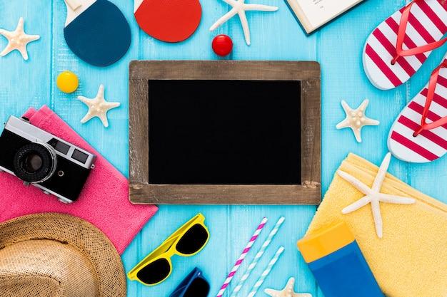 Definido para umas férias no mar praia: toalha, óculos de sol, quadro-negro e suncream