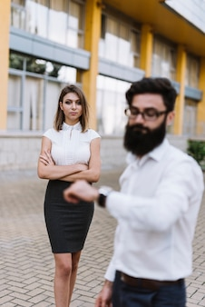 Defocused jovem empresário olhando para o relógio de pulso com elegante jovem de pé no fundo