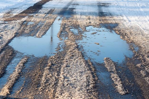 Degelo da primavera. poças de neve derretida na rua.