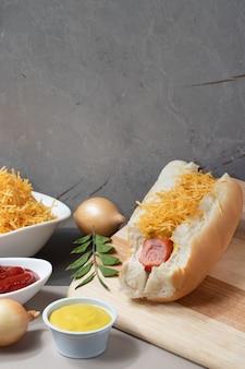 Degustação de cachorro-quente tradicional com ketchup, mostarda e palha de batata.
